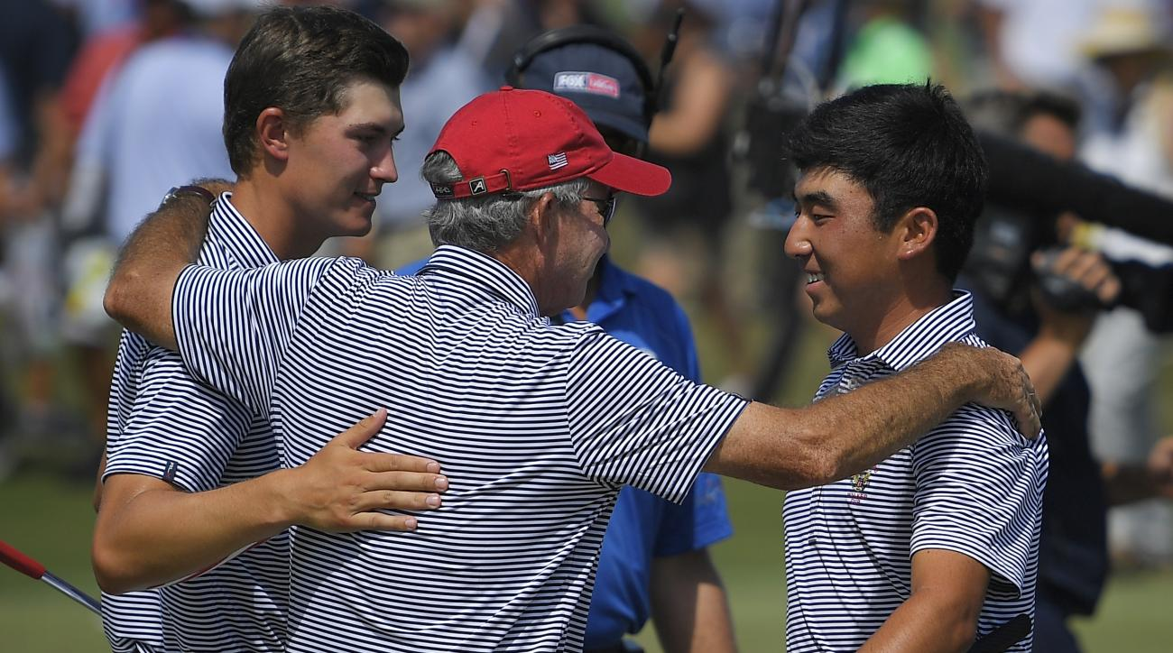Captain Spider Miller, center, of the United States, embraces Maverick McNealy, left, and Doug Ghim after they completed their round during foursomes at the Walker Cup golf matches at Los Angeles Country Club, Sunday, Sept. 10, 2017, in Los Angeles. (AP P