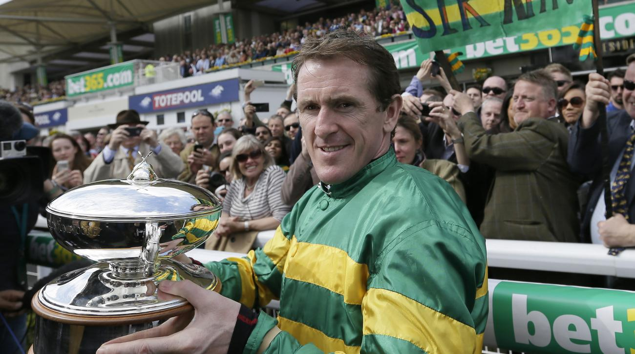 Jockey Tony McCoy tours the parade ring after he received the champion jump jockey's trophy, which he has been given permanently, before the last races of his career at  at Sandown Park racecourse, London, Saturday, April 25, 2015. McCoy was champion jump