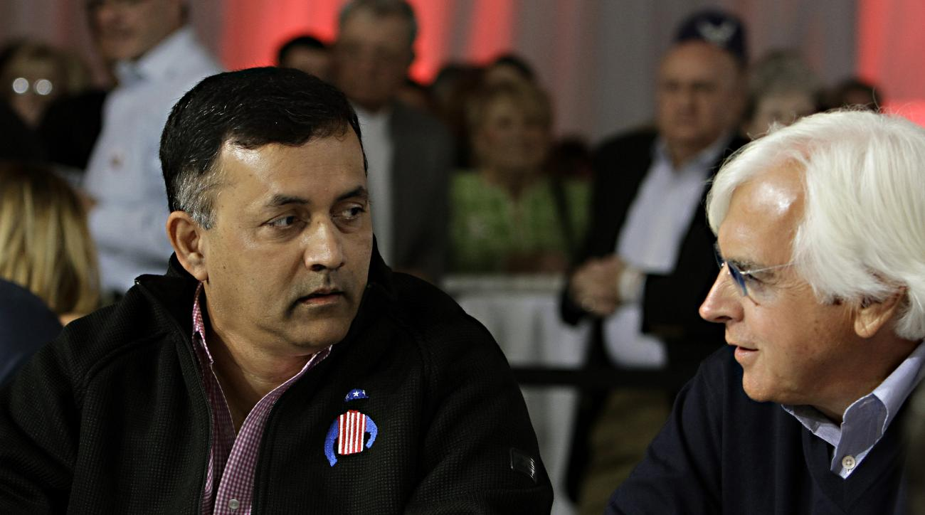 Kentucky Derby entrant Dortmund owner Kaleem Shah, left, talks with trainer Bob Baffert, right, before the start of the post position draw at Churchill Downs in Louisville, Ky., Wednesday, April 29, 2015.  (AP Photo/Garry Jones)