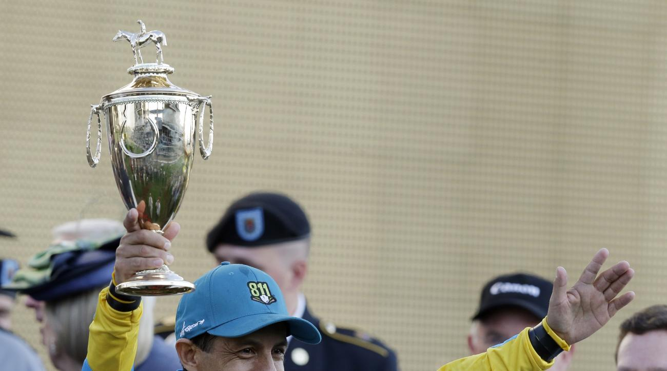 Victor Espinoza holds the trophy after riding American Pharoah to victory in the 141st running of the Kentucky Derby horse race at Churchill Downs Saturday, May 2, 2015, in Louisville, Ky.  (AP Photo/Brynn Anderson)