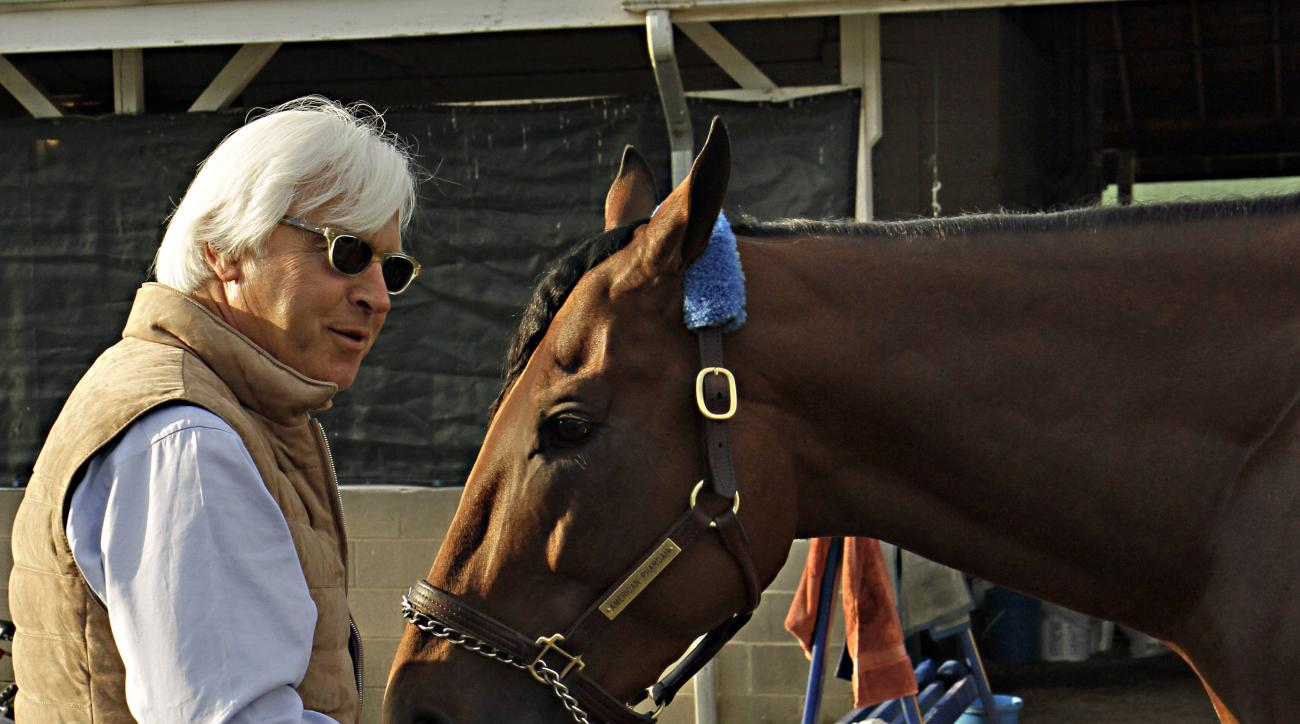 Hall of Fame trainer Bob Baffert, left, feeds Kentucky Derby winner American Pharoah a carrot at Churchill Downs in Louisville, Ky., Sunday, May 3, 2015. Baffert won his fourth Derby, and first since 2002.  (AP Photo/Garry Jones)