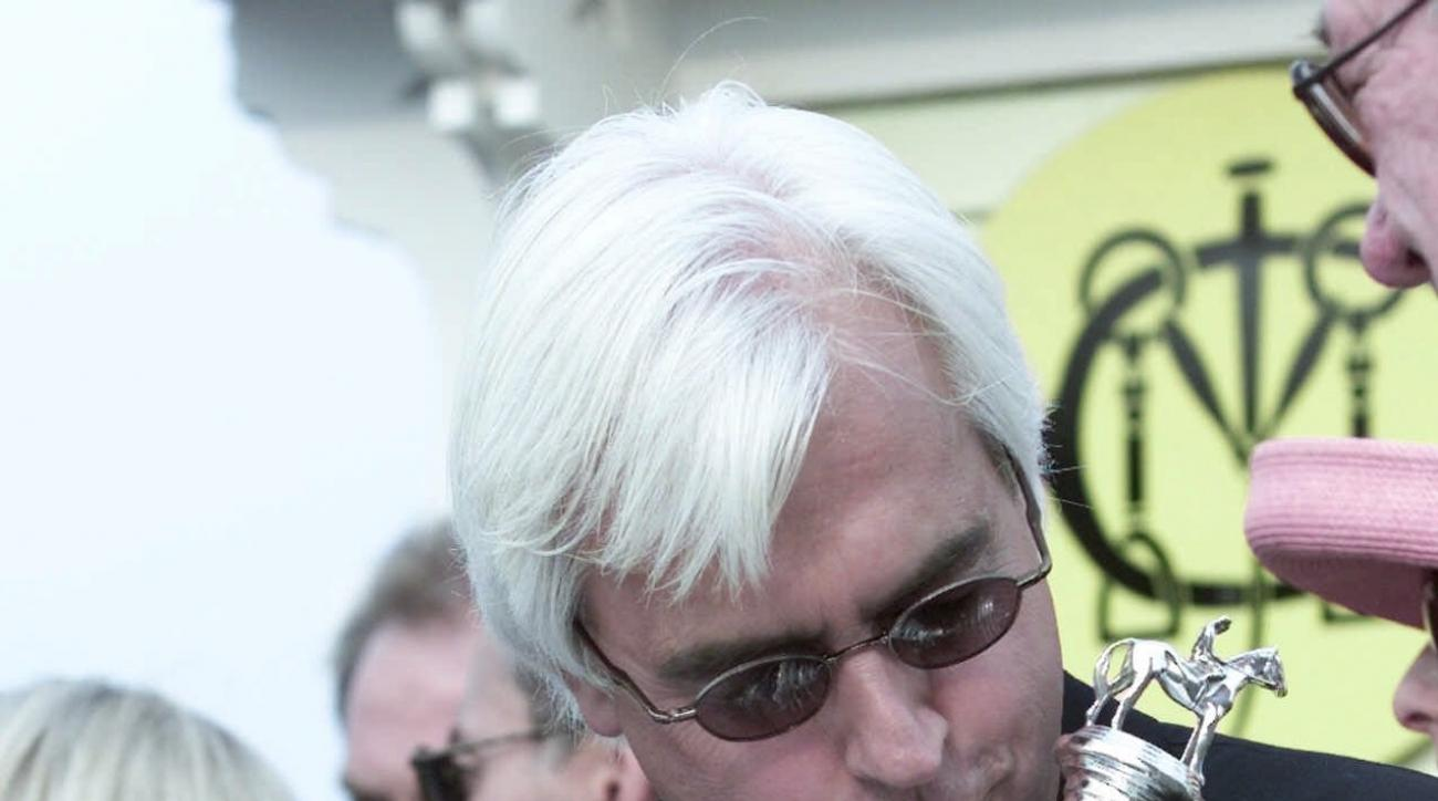 ADVANCE FOR WEEKEND EDITIONS, MAY 8-10 - FILE - In this May 19, 2001, file photo, Point Given trainer Bob Baffert holds the trophy in the winners circle after the Preakness horse race at Pimlico Race Course in Baltimore. Baffert has a stellar record at th