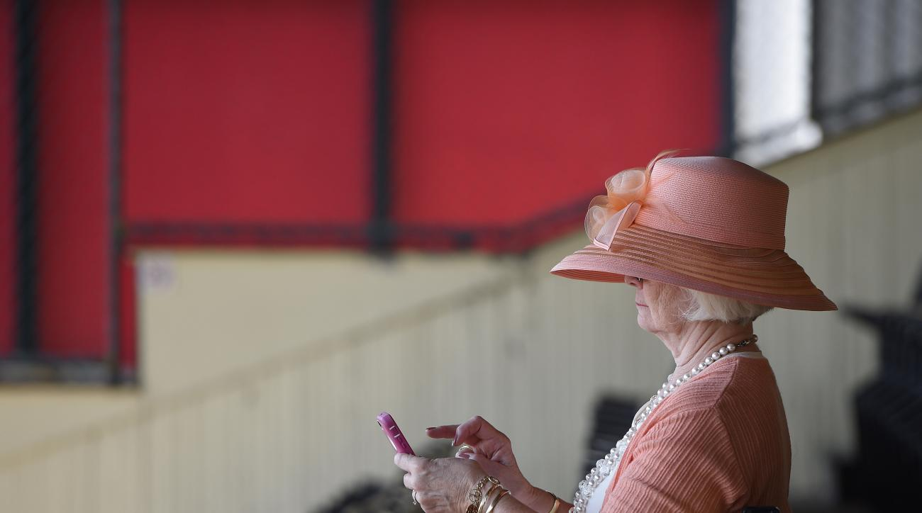 Sandy Wiebel, of Boonsboro, Md., looks over her phone before the 140th Preakness Stakes horse race at Pimlico Race Course, Saturday, May 16, 2015, in Baltimore. (AP Photo/Nick Wass)