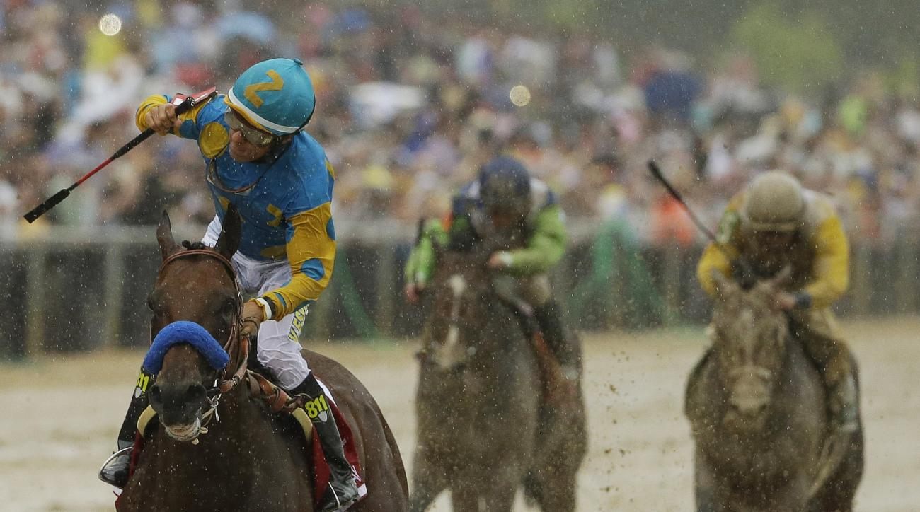 American Pharoah, ridden by Victor Espinoza, left, wins the 140th Preakness Stakes horse race at Pimlico Race Course, Saturday, May 16, 2015, in Baltimore. (AP Photo/Matt Slocum)