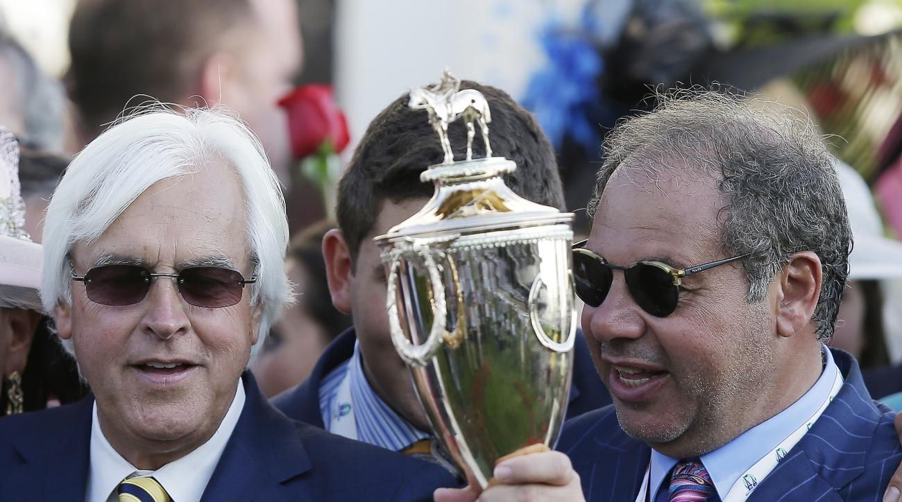 FILE- In this May 2, 2015, file photo, trainer Bob Baffert, left, holds up the winning trophy alongside Ahmed Zayat, owner of American Pharoah, after American Pharoah won the 141st running of the Kentucky Derby horse race at Churchill Downs in Louisville,