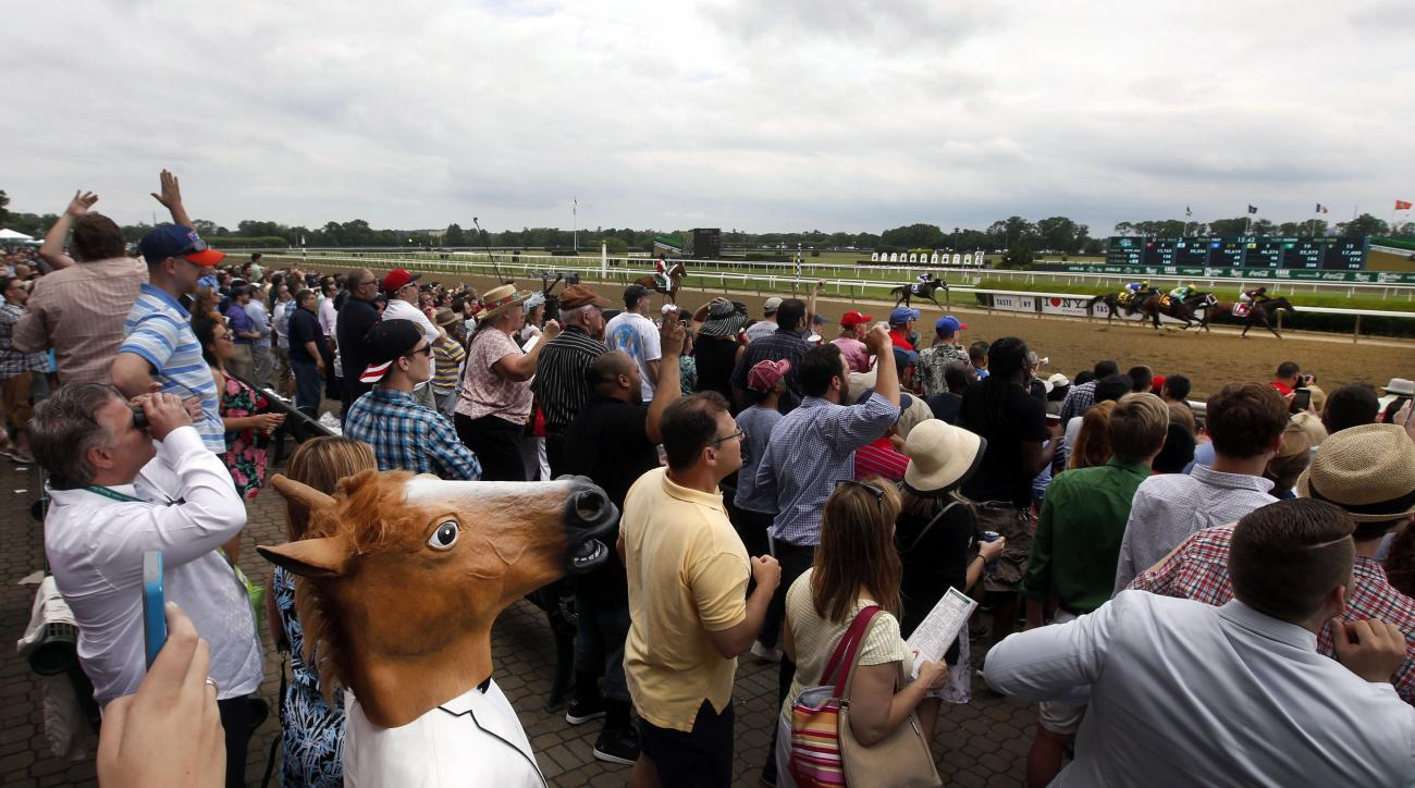 A spectator wearing a horse mask watches the third race of the day prior to the 147th running of the Belmont Stakes horse race at Belmont Park, Saturday, June 6, 2015, in Elmont, N.Y.  American Pharoah will try for a Triple Crown when he runs in Saturday'