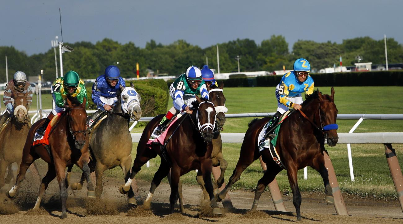 American Pharoah (5), far right, leads the field entering turn three on the way to a Triple Crown victory during the 147th running of the Belmont Stakes horse race at Belmont Park, Saturday, June 6, 2015, in Elmont, N.Y. (AP Photo/Jason DeCrow)