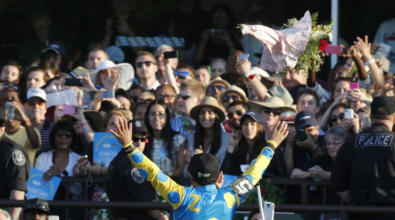Victor Espinoza reacts to the crowd after guiding American Pharoah to win the 147th running of the Belmont Stakes horse race at Belmont Park, Saturday, June 6, 2015, in Elmont, N.Y. American Pharoah is the first horse to win the Triple Crown since Affirme