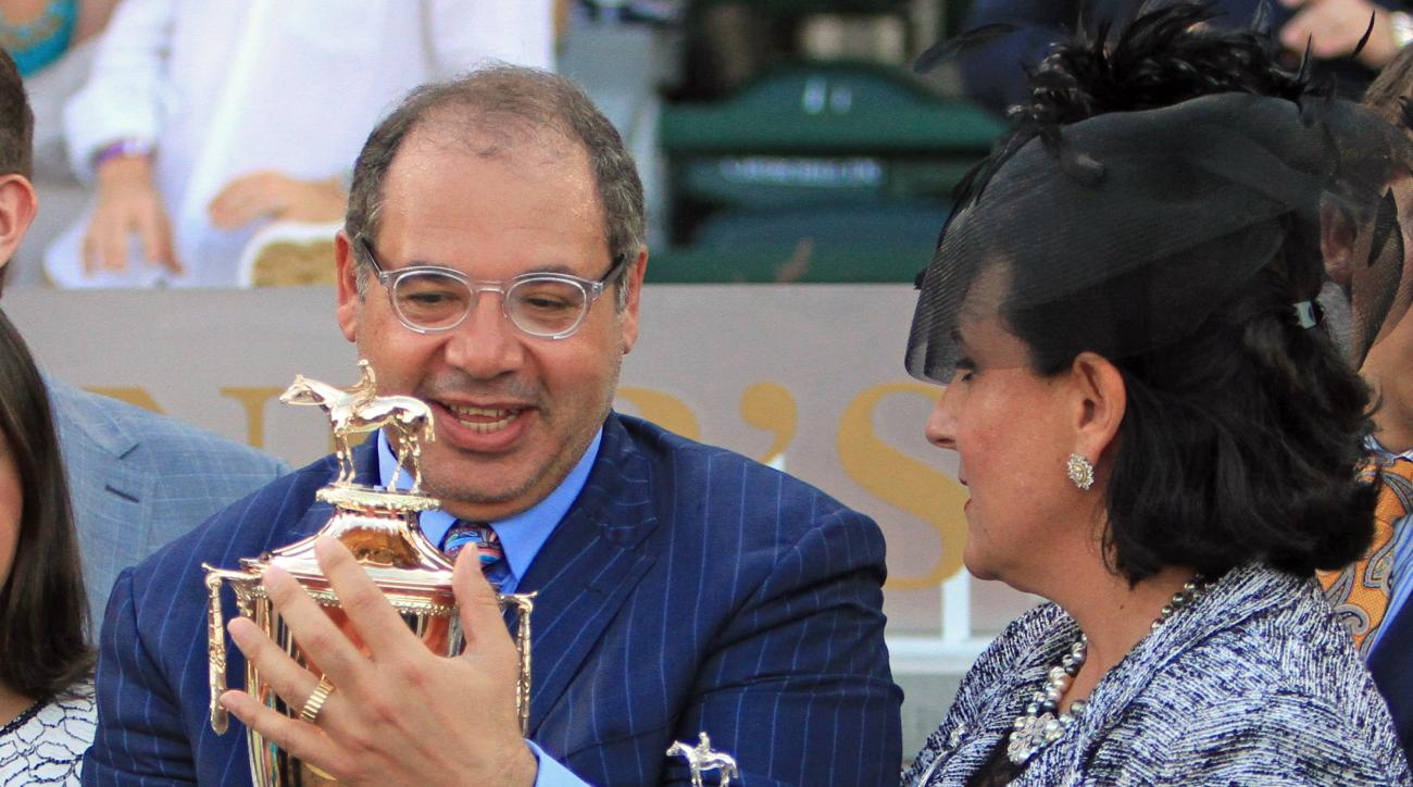 Thoroughbred owner/breeder Ahmed Zayat and his wife Joanne, right, admire the engraved Kentucky Derby trophy, won by American Pharoah on the first Saturday in May, at Churchill Downs in Louisville, Ky., Saturday, June 13, 2015.  (AP Photo/Garry Jones)