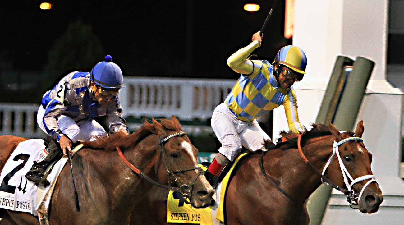 Jockey Shaun Bridgmohan, right, celebrates after guiding Noble Bird to a narrow victory over Lea, left, ridden by Joel Rosario, in the Stephen Foster Handicap horse race at Churchill Downs in Louisville, Ky., Saturday, June 13, 2015.  (AP Photo/Garry Jone