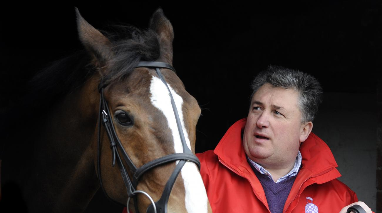 FILE - In this Wednesday, Feb. 24, 2010 file photo, racehorse trainer Paul Nicholls stands next to Cheltenham Gold Cup hope, Kauto Star at Manor Farm Stables in Ditcheat, western England. Kauto Star, one of Britain's greatest and most popular racehorses,