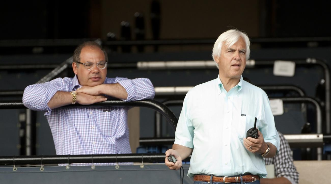 In this photo provided by Benoit Photo, Triple Crown winner American Pharoah owner Ahmed Zayat, left, and trainer Bob Baffert watch from the grandstand as American Pharoah runs six furlongs at Del Mar Racetrack in Del Mar, Calif., Thursday, July 23, 2015.