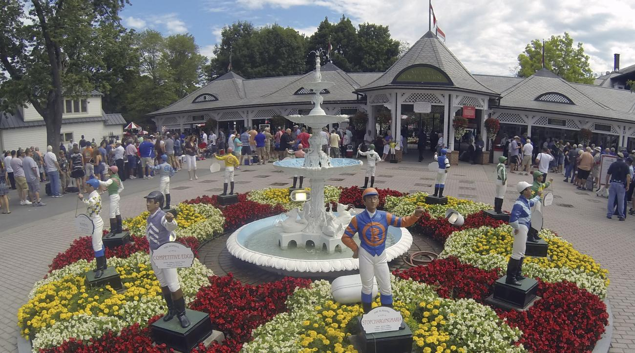 Race fans wait for the gates to open on opening day of the horse racing season at Saratoga Race Course in Saratoga Springs, N.Y., Friday, July 24, 2015. (AP Photo/Hans Pennink)