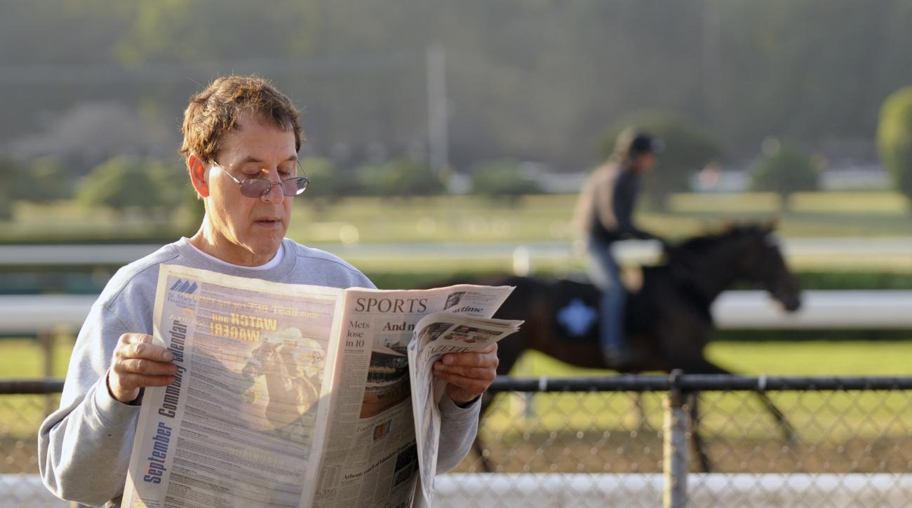 Jon Guarino of Beekman, N.Y., looks at a newspaper while waiting for racing action to start on Travers Day at Saratoga Race Course in Saratoga Springs, N.Y., Saturday, Aug. 29, 2015. (AP Photo/Hans Pennink)