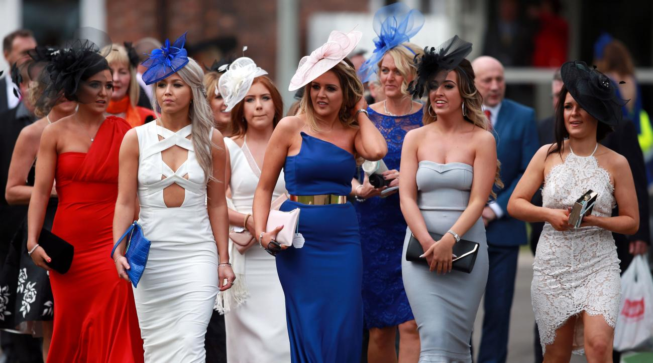 Racegoers promonade as they arrive for the start of Ladies Day of the Grand National Festival at Aintree Racecourse, Liverpool, England, Friday April 8, 2016. The Grand National Festival is one of the top horse race events of the year. (David Davies / PA