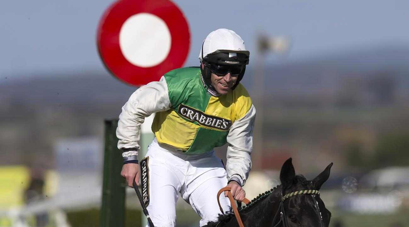 FILE - This is a Saturday, April 11, 2015 file photo of  jockey Leighton Aspell as he smiles after winning the Grand National horse race aboard Many Clouds at Aintree Racecourse Liverpool, England. Leighton Aspell made a heat-of-the-moment decision to ret