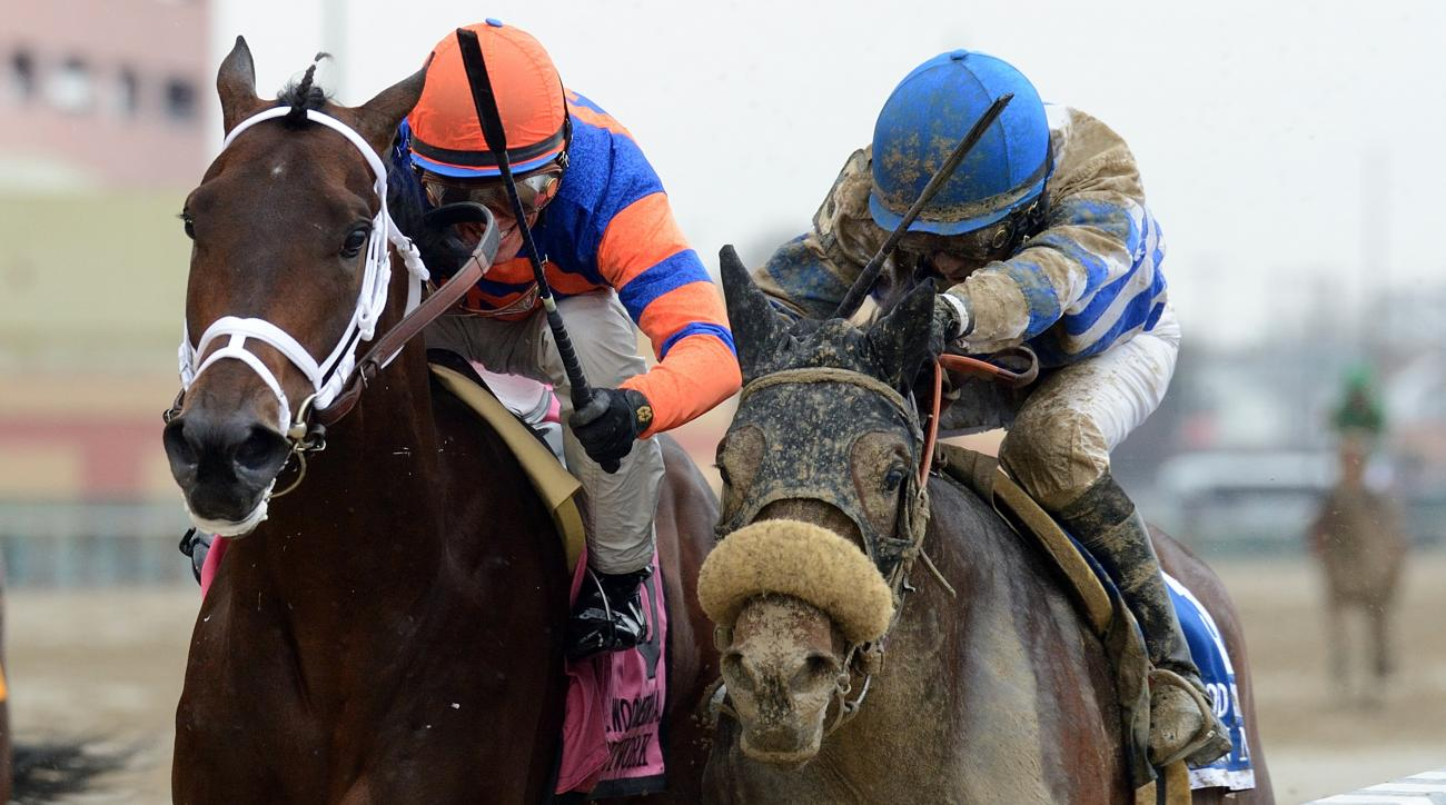 In this image provided by the Coglianese Photos, Outwork, second from right, ridden by John Velazquez, noses out Trojan Nation, ridden by Aaron Gryder, to win the Wood Memorial horse race, Saturday, April 9, 2016, at Aqueduct in New York. (Coglianese Phot