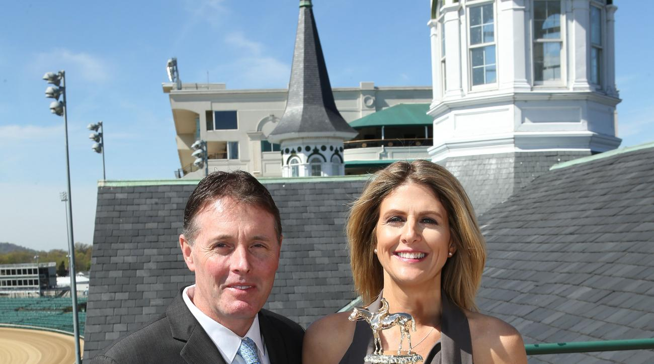 In this image provided by Churchill Downs, Artisans Bill Juaire and Susanne Blackinton-Juaire of LeachGarner, who crafted and delivered the trophy for the 142nd Kentucky Derby, pose with it at Churchill Downs, Wednesday, April 13, 2016, in Louisville, Ky.