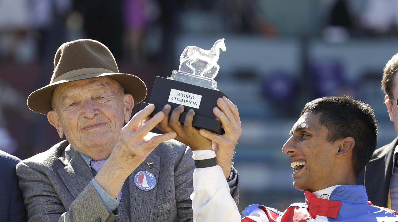 FILE - In ths Nov. 12, 2012, file photo, owner/breeder Fred Bradley, left, holds up the trophy with jockey Rajiv Maragh in the winner's circle after Groupie Doll won the Breeders' Cup Filly & Mare Sprint horse race at Santa Anita Park in Arcadia, Calif. B
