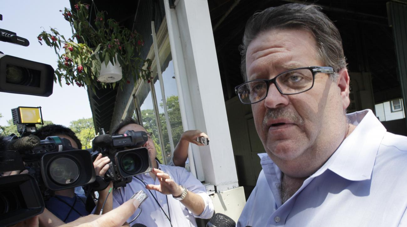 FILE - In this June 8, 2012, file photo, horse trainer Dale Romans talks with reporters outside Barn 2 at Belmont Park in Elmont, N.Y. Romans counts himself lucky that he and three passengers did not suffer life-threatening injuries in a car crash while l