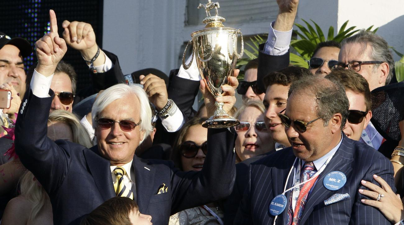 FILE - In this Saturday, May 2, 2015 file photo, American Pharoah trainer Bob Baffert, left, and owner Ahmed Zayat hold the trophy after Victor Espinoza rode American Pharoah to victory in the 141st running of the Kentucky Derby horse race at Churchill Do
