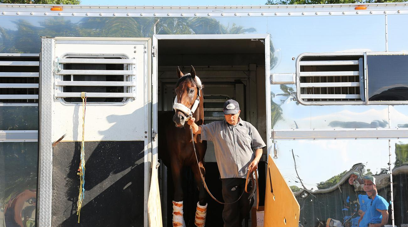 In a photo provided by Equi-Photo, Kentucky Derby champion Nyquist is escorted off the van by groom Elias Anaya after arriving at Monmouth Park in Oceanport, N.J., on Wednesday afternoon, July 27, 2016, after a flight from California. Nyquist will take on