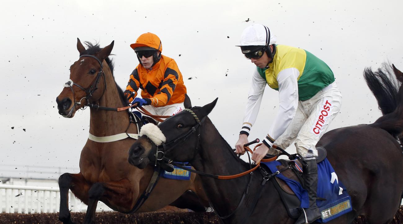 Many Clouds  ridden by Leighton Aspell, right, jump an early fence in company with Thistlecrack ridden by Tom Scudamore before going on to win The Cotswold Chase Race run during Festival Trials Day at Cheltenham Racecourse, in Cheltenham, England, Saturda
