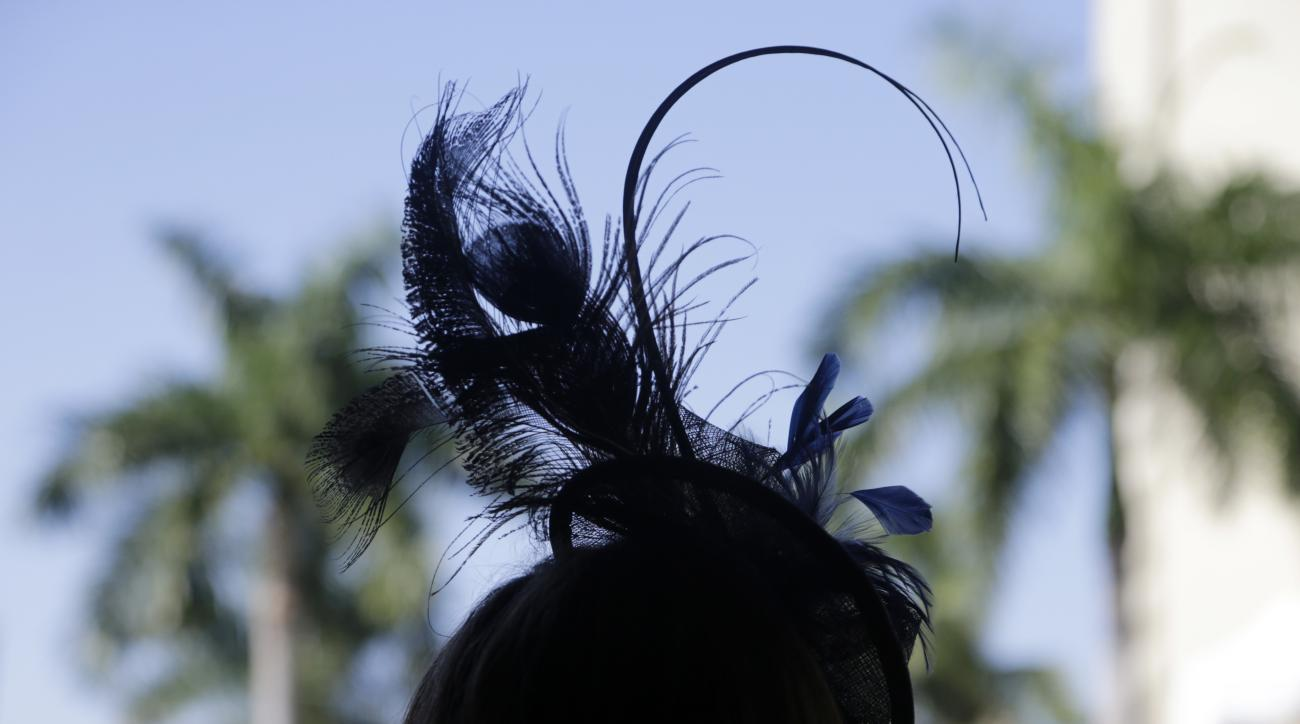 A woman wearing a stylish hat stands in the paddock before the inaugural running of the $12 million Pegasus World Cup horse race at Gulfstream Park, Saturday, Jan. 28, 2017, in Hallandale Beach, Fla. (AP Photo/Lynne Sladky)