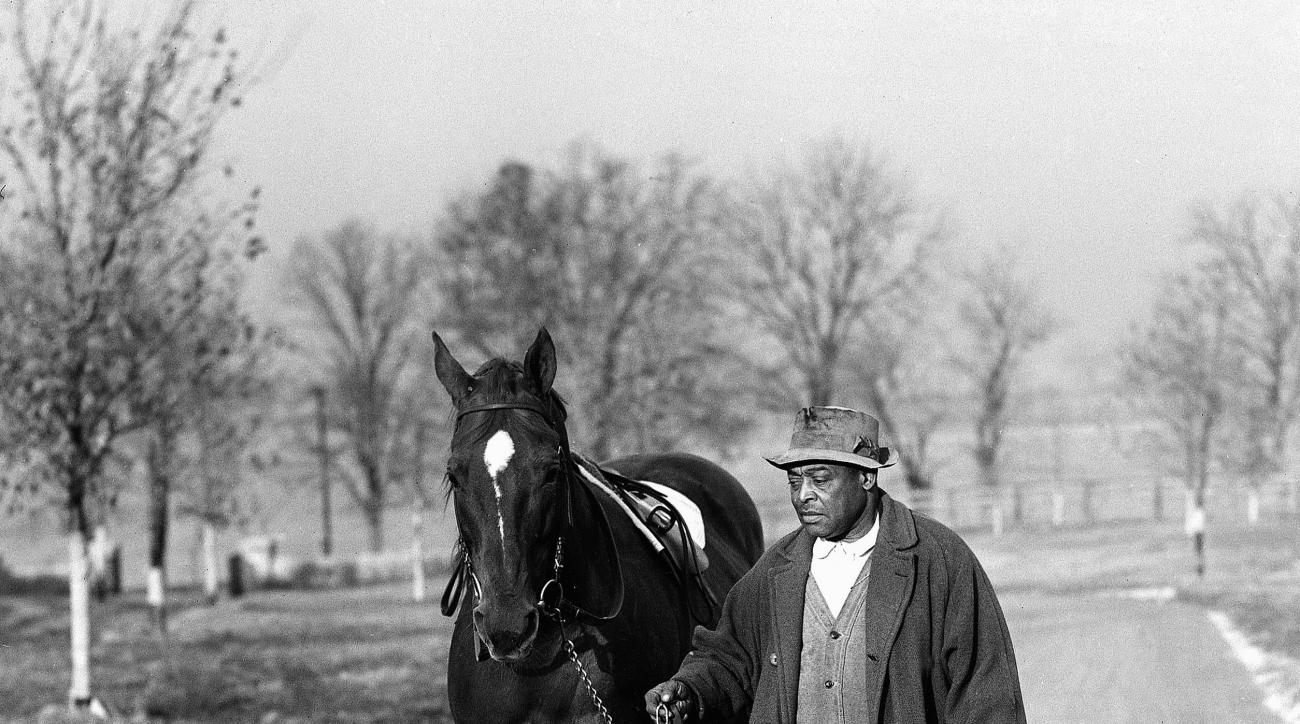 FILE - In this Nov. 25, 1939, file photo, Man o' War is led back to the barn by his lifetime caretaker and groom, Will Harbut, after exercising in Lexington, Ky. The Kentucky Derby Museum says it is planning a new exhibit next month on one of thoroughbred