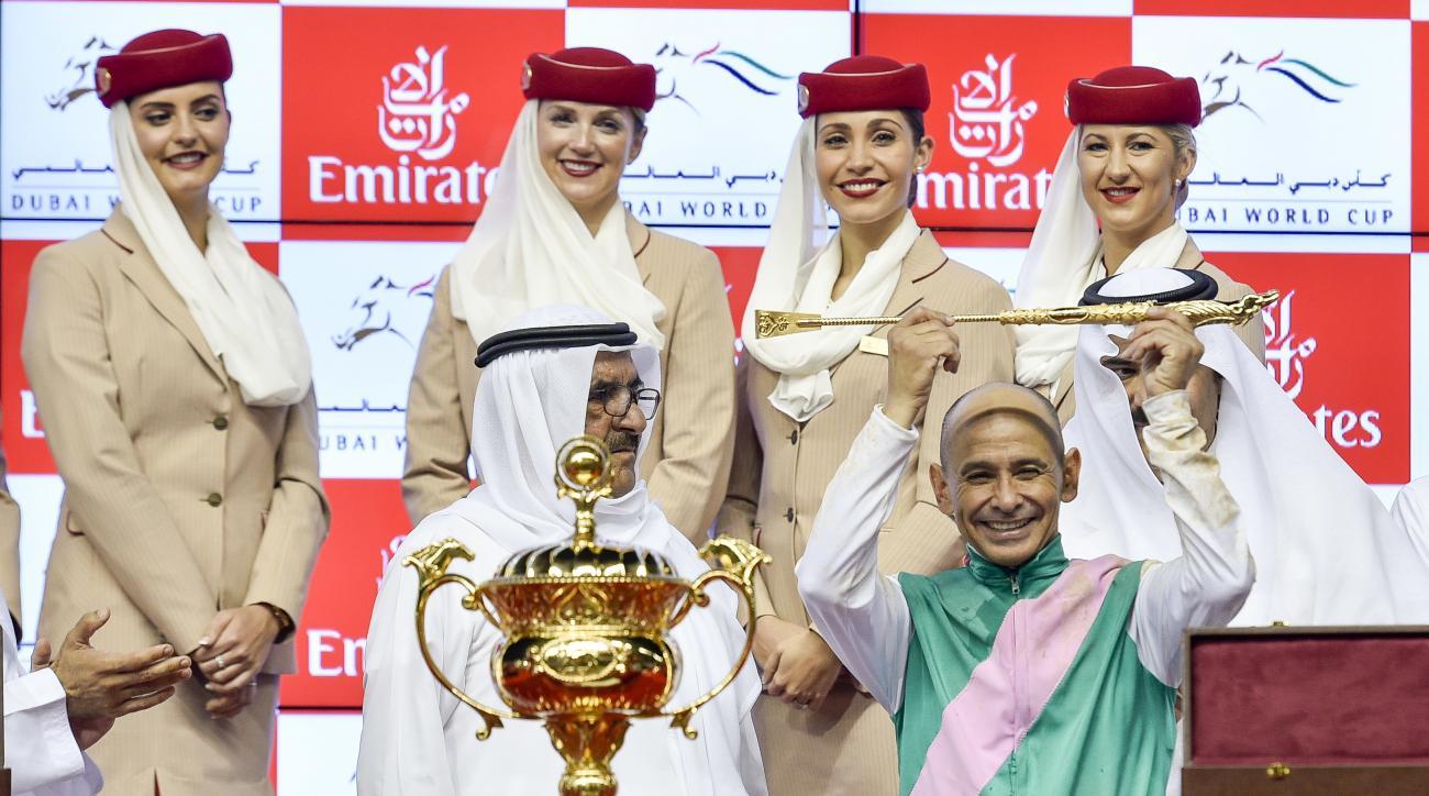Mike Smith, jockey of Saudia Arabia, bottom right, celebrates with the Deputy Ruler of Dubai, Sheikh Hamdan bin Rashid Al Maktoum, as he holds the golden whip after winning the U.S. $ 10,000,000 Dubai World Cup horse racing at the Meydan Racecourse in Dub