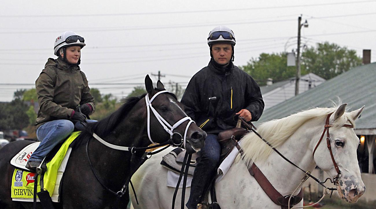 Trainer Joe Sharp right leads Kentucky Derby entrant Girvin left ridden by his wife Rosie Napravnik a former jockey back to Barn 33 following a morning gallop at Churchill Downs in Louisville Ky. Thursday