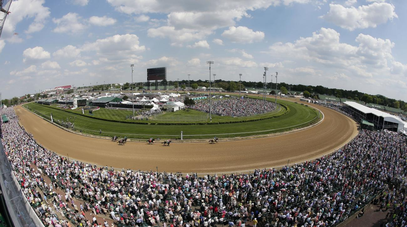 FILE - In this May 2, 2015, file photo, taken with a fisheye lens, fans watch a race before the 141st running of the Kentucky Derby horse race at Churchill Downs in Louisville, Ky. Churchill Downs' parent company has pumped $250 million into renovations s