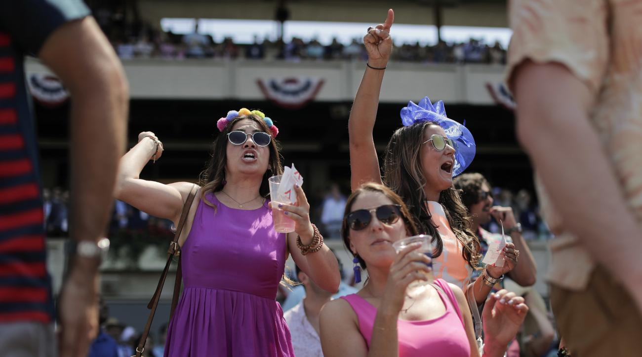 Horse racing fans react as thoroughbreds make their way around the track during the sixth race before the 149th running of the Belmont Stakes horse race, Saturday, June 10, 2017, in Elmont, N.Y. (AP Photo/Julie Jacobson)