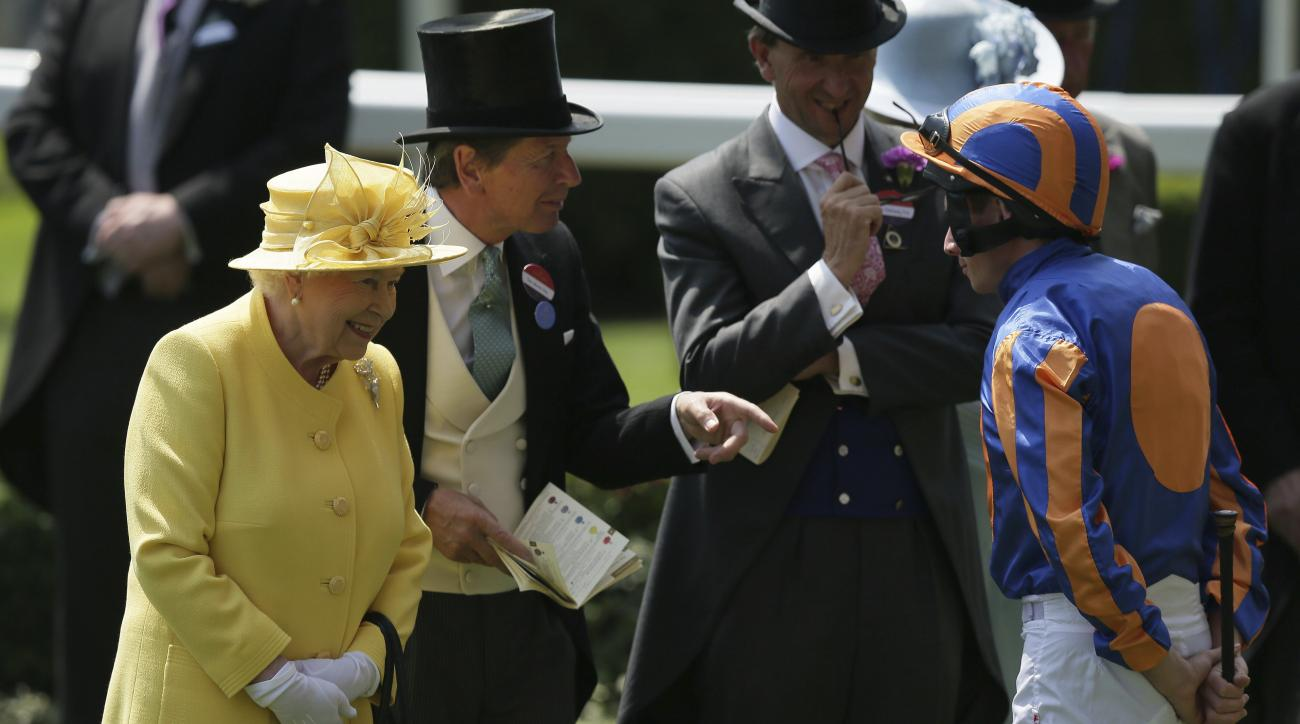 Britain's Queen Elizabeth II speaks with jockey Ryan Moore, right, and racing manager John Warren, second left, after arriving in the parade ring on the second day of the Royal Ascot horse race meeting in Ascot, England, Wednesday, June 21, 2017. (AP Phot