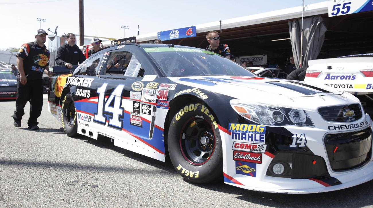 The pit crew for NASCAR Sprint Cup Series driver Tony Stewart (14) push his car to the inspection station at Richmond International Raceway in Richmond, Va., Friday, April 24, 2015. (AP Photo/Scott P. Yates)