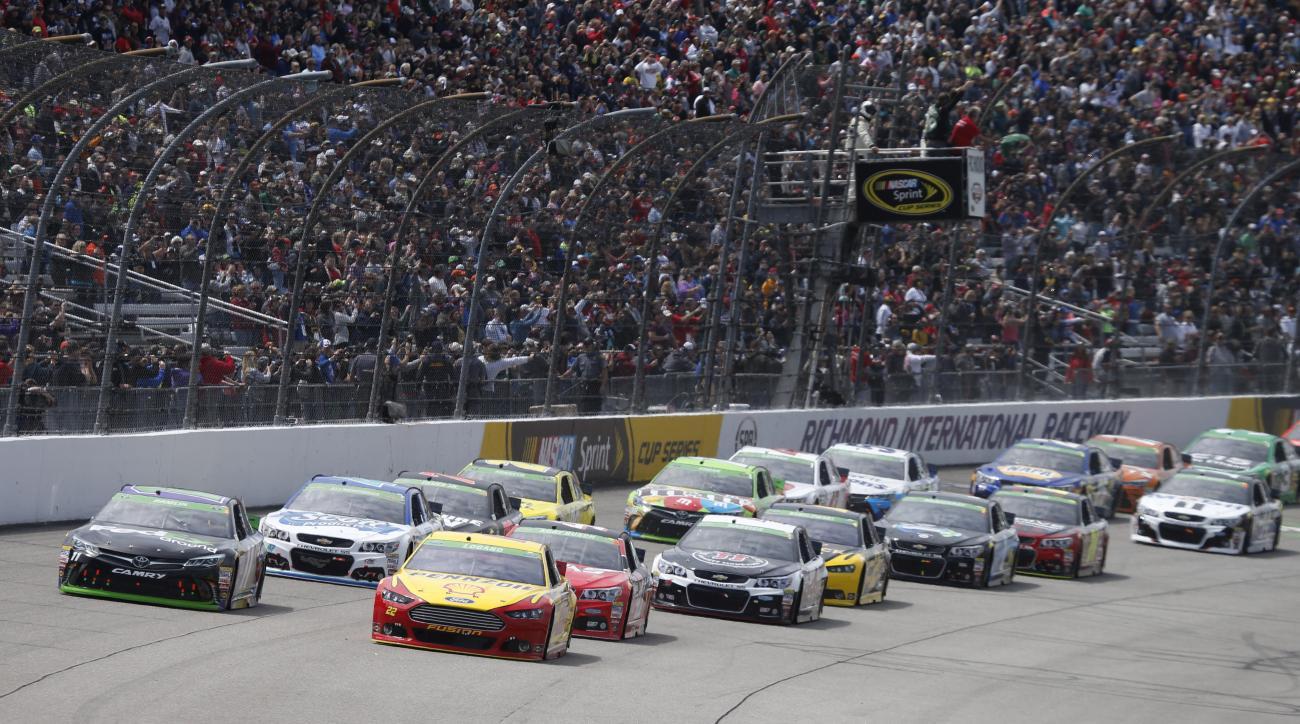 Joey Logano (22) and Denny Hamlin (11) lead the field at he start of the NASCAR Sprint Cup auto race at Richmond International Raceway in Richmond, Va., Sunday, April 26, 2015. (AP Photo/Steve Helber)