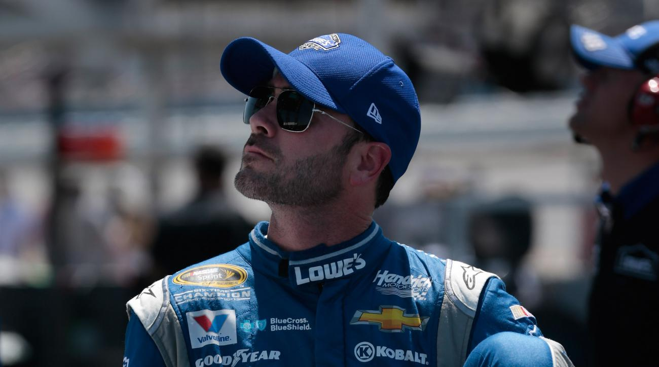 Driver Jimmie Johnson climbs out of his car during qualifying for the NASCAR Sprint Cup Series auto race at Talladega Superspeedway, Saturday, May 2, 2015, in Talladega, Ala. (AP Photo/Butch Dill)