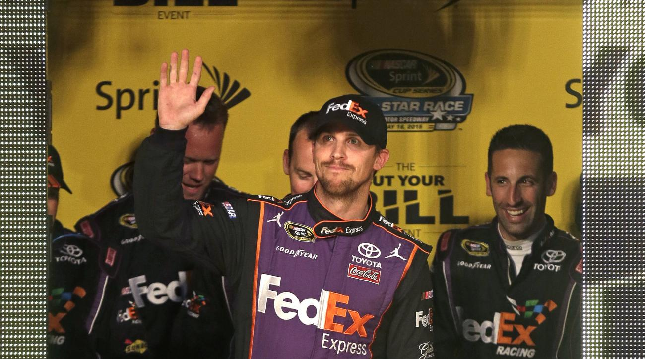 Denny Hamlin waves during driver introductions for the NASCAR Sprint All-Star auto race at Charlotte Motor Speedway in Concord, N.C., Saturday, May 16, 2015. Hamlin won the pole position for the race. (AP Photo/Gerry Broome)