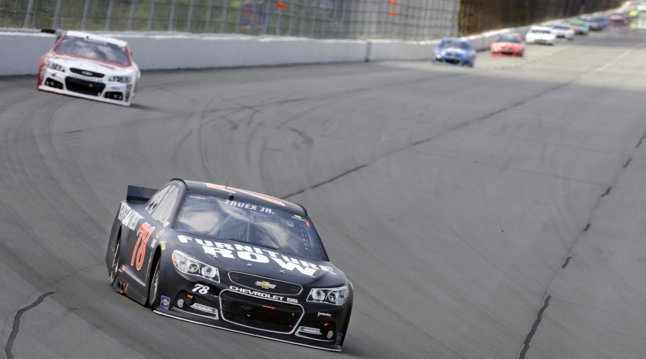 Martin Truex Jr. (78) leads Kevin Harvick (4) through turn one during a NASCAR Sprint Cup Series auto race at Pocono Raceway in Long Pond, Pa., Sunday, June 7, 2015. (AP Photo/Mel Evans)
