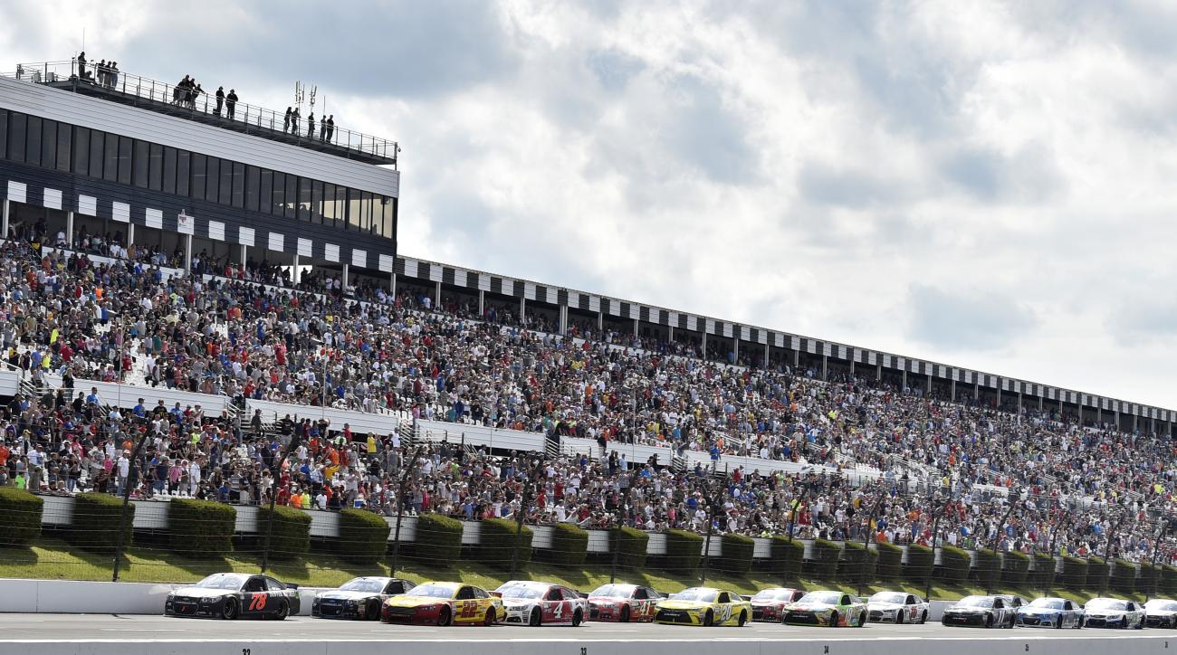 Martin Truex Jr. (78) leads Joey Logano (22), Jimmie Johnson (48) and Kevin Harvick (4) on a late restart in a NASCAR Sprint Cup Series auto race at Pocono Raceway in Long Pond, Pa., Sunday, June 7, 2015. (AP Photo/Derik Hamilton)