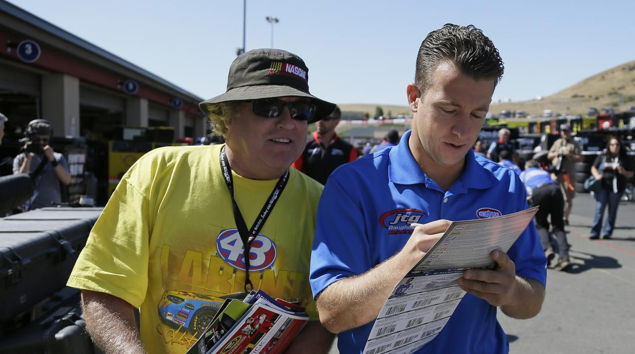 A.J. Allmendinger, right, signs autographs in the garage area before practice for the NASCAR Sprint Cup Series auto race Friday, June 26, 2015, in Sonoma, Calif. Allmendinger earned a spot in the championship race with a win on a road course. He'll try to