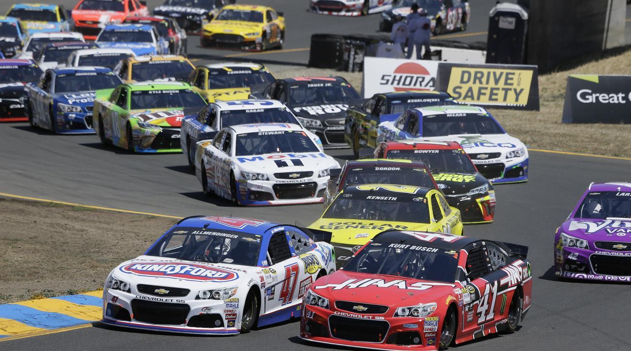 A.J. Allmendinger (47) and Kurt Busch (41) make their through Turn 2 at the start of the NASCAR Sprint Cup Series auto race Sunday, June 28, 2015, in Sonoma, Calif. (AP Photo/Eric Risberg)