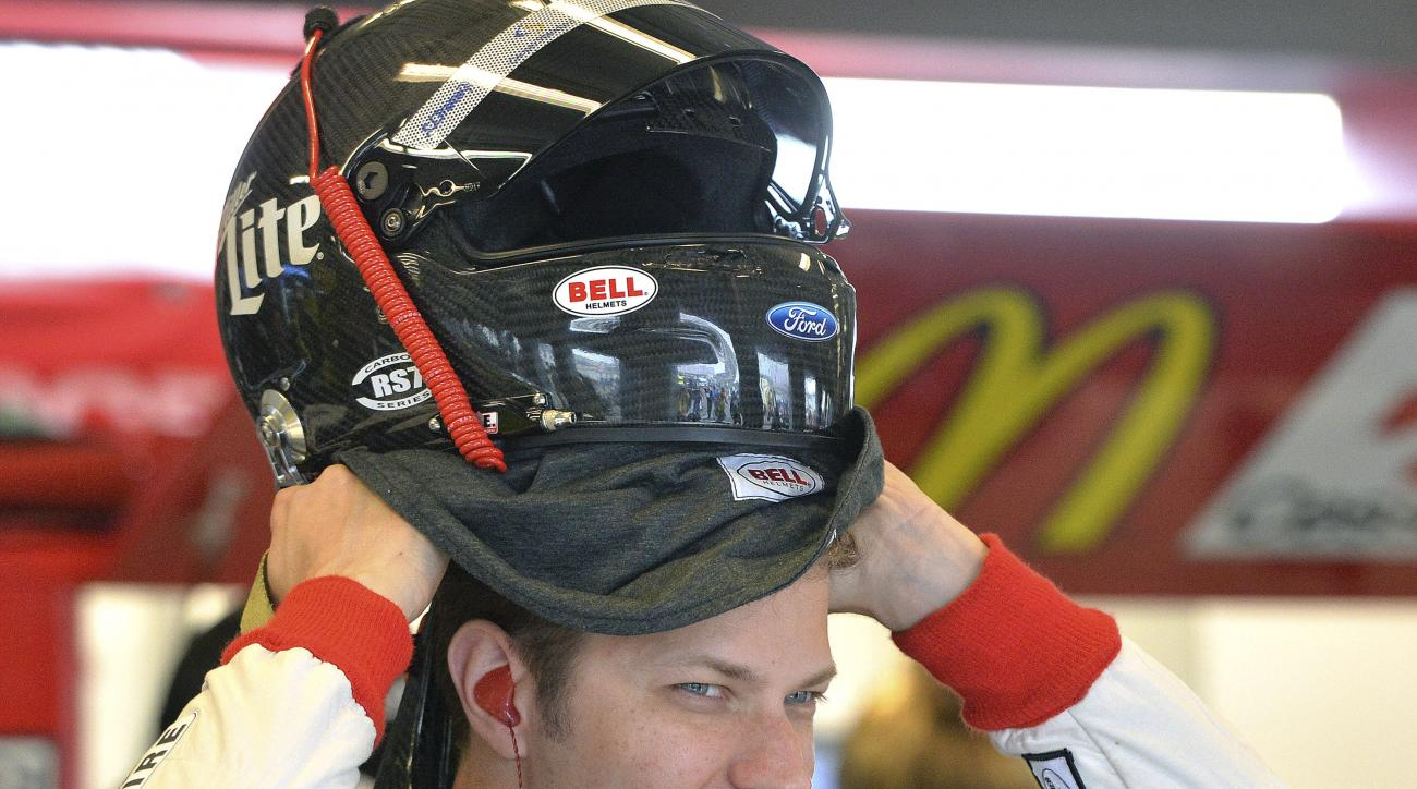 Brad Keselowski puts on his helmet in anticipation of the end of the rain delay of practice for the NASCAR Xfinity series auto race at Kentucky Speedway in Sparta, Ky., Friday, July 10, 2015. Rain has been an issue, causing scheduled practice sessions to