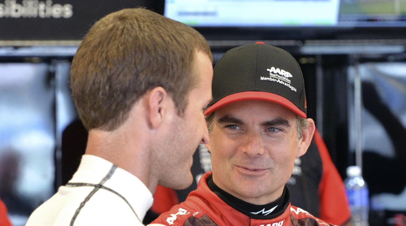 Jeff Gordon, right, talks with Kasey Kahne as they wait for the track to dry so practice may resume before the NASCAR Xfinity series auto race at Kentucky Speedway in Sparta, Ky., Friday, July 10, 2015. (AP Photo/Timothy D. Easley)