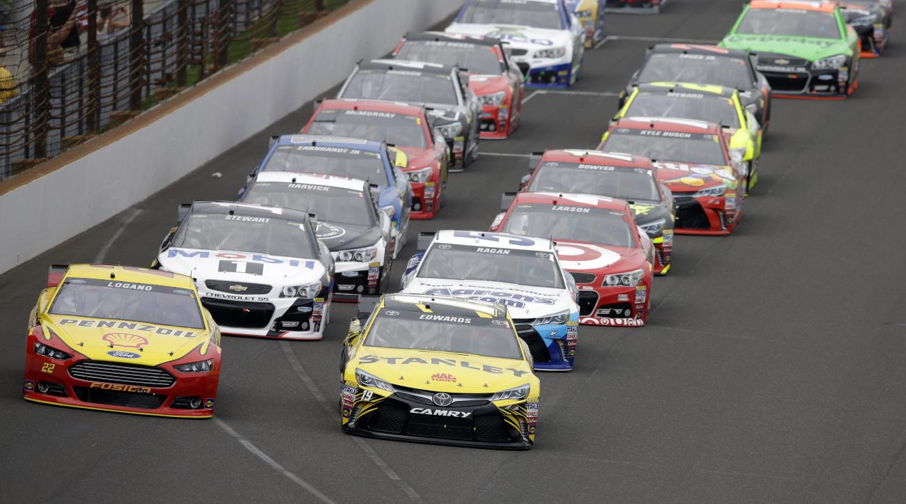 Sprint Cup Series drivers Carl Edwards (19) and Joey Logano (22) lead the field into the first turn on the start of the NASCAR Brickyard 400 auto race at Indianapolis Motor Speedway in Indianapolis, Sunday, July 26, 2015.  (AP Photo/Darron Cummings)