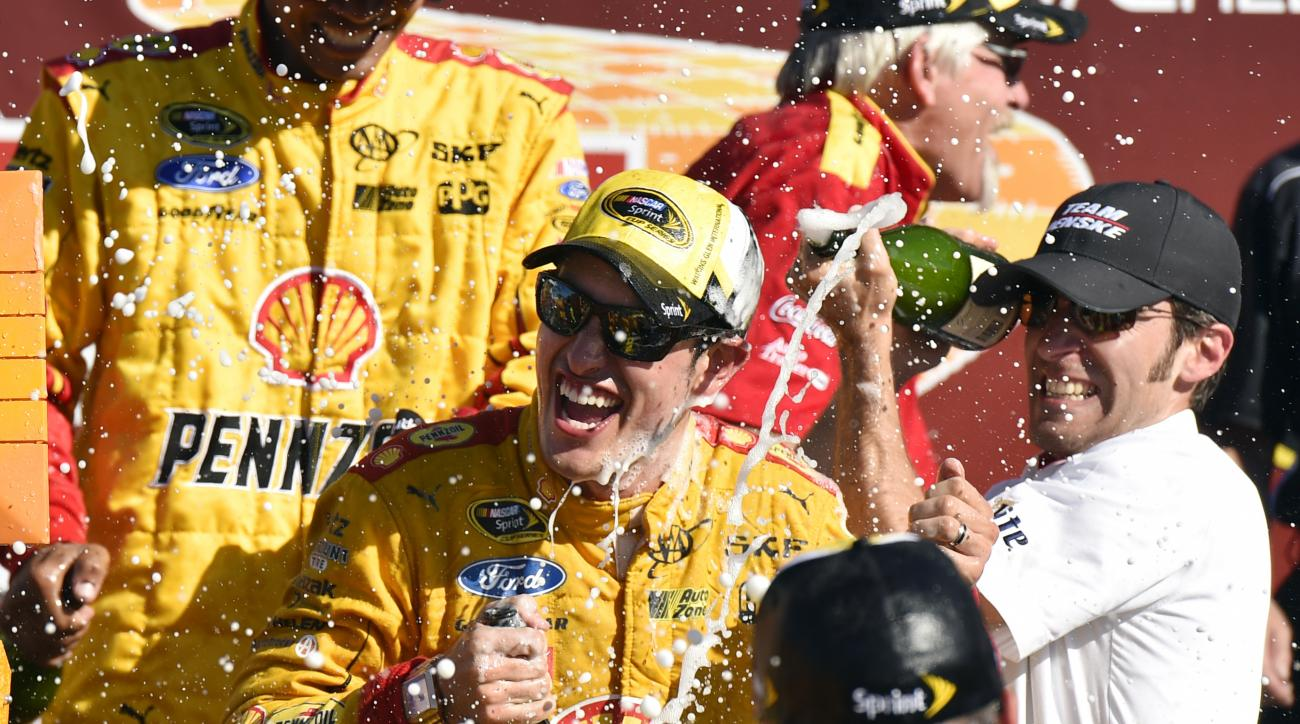 Joey Logano celebrates in the victory lane after winning a NASCAR Sprint Cup series auto race at Watkins Glen International, Sunday, Aug. 9, 2015, in Watkins Glen. N.Y. (AP Photo/Derik Hamilton)