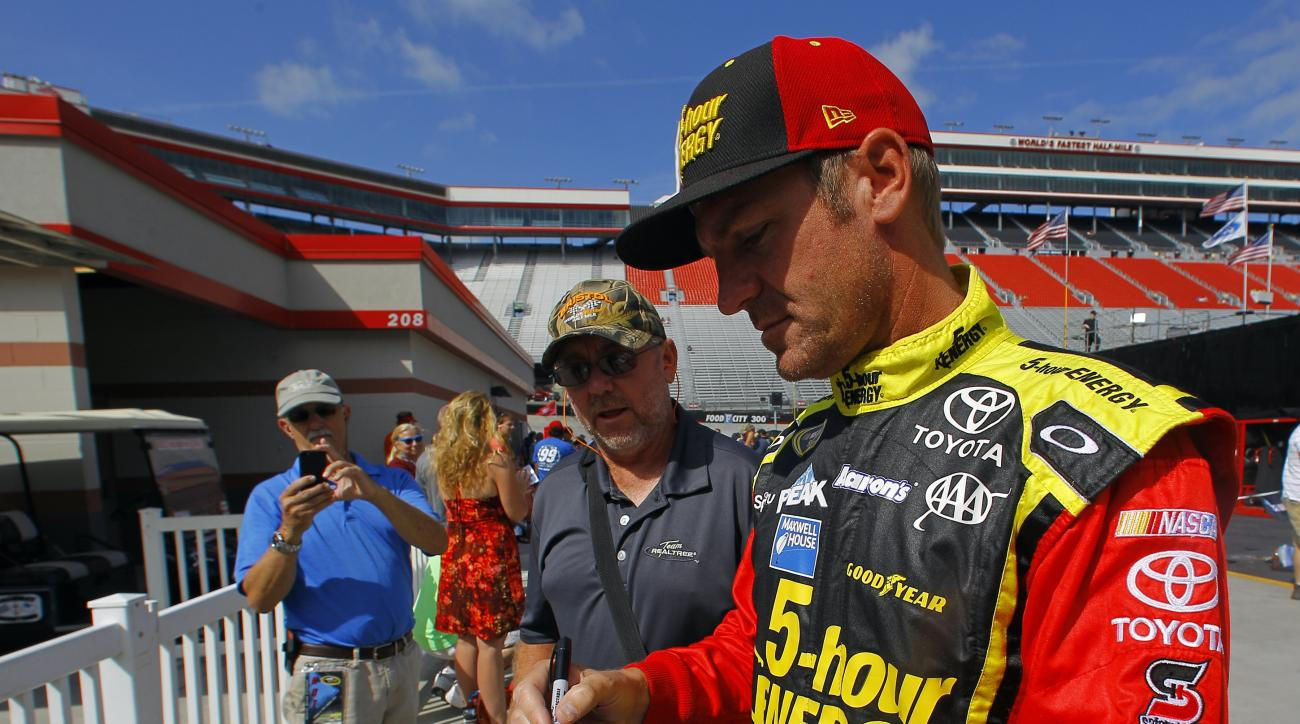 Driver Clint Boyer signs an autograph before practice for the NASCAR Sprint Cup Series Irwin Tools Night Race, Friday, Aug. 21, 2015,  in Bristol, Tenn. (AP Photo/Wade Payne)