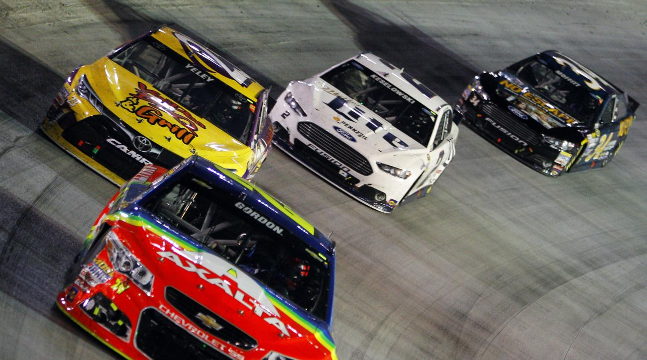 Jeff Gordon (24) drives through a turn in fron tof JJ Yeley (23), Brad Keselowski (2) and Brett Moffitt (34) during the NASCAR Sprint Cup Series auto race, Saturday, Aug. 22, 2015, in Bristol, Tenn. (AP Photo/Wade Payne)