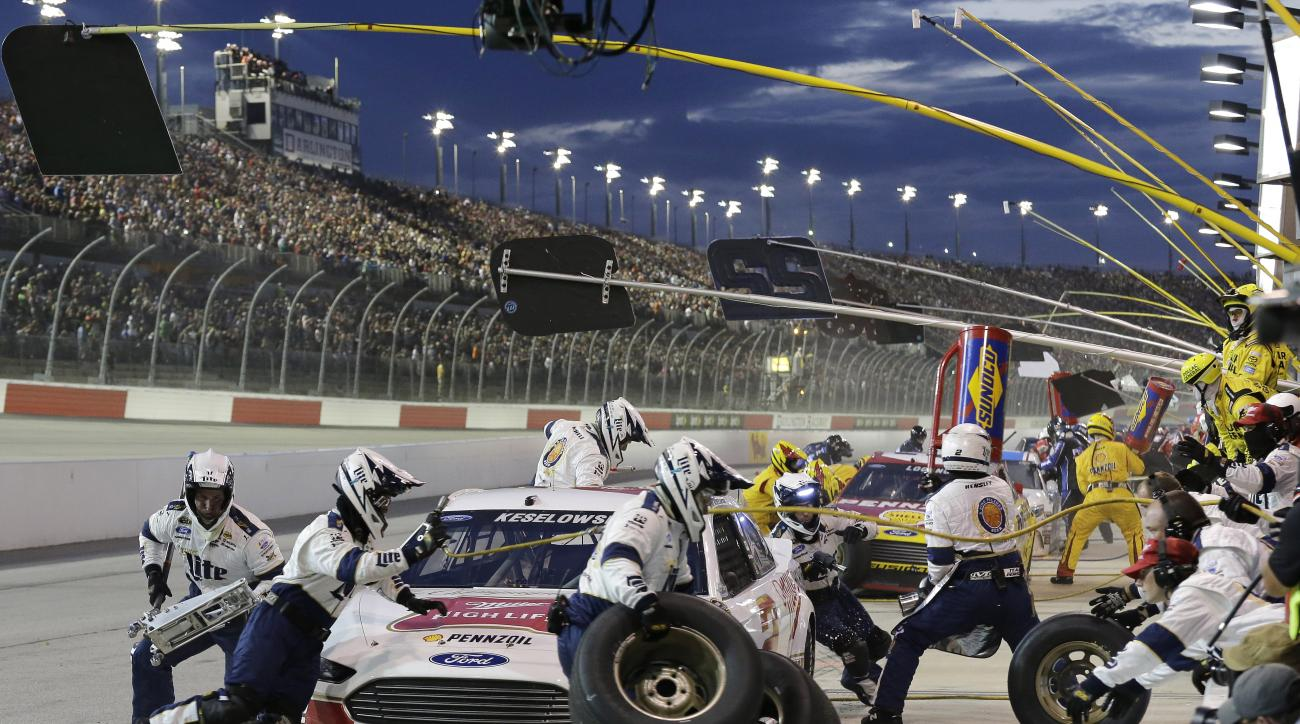 Crew members for Brad Keselowski perform a pit stop during a NASCAR Sprint Cup auto race at Darlington Raceway, Sunday, Sept. 6, 2015, in Darlington, S.C. (AP Photo/Terry Renna)