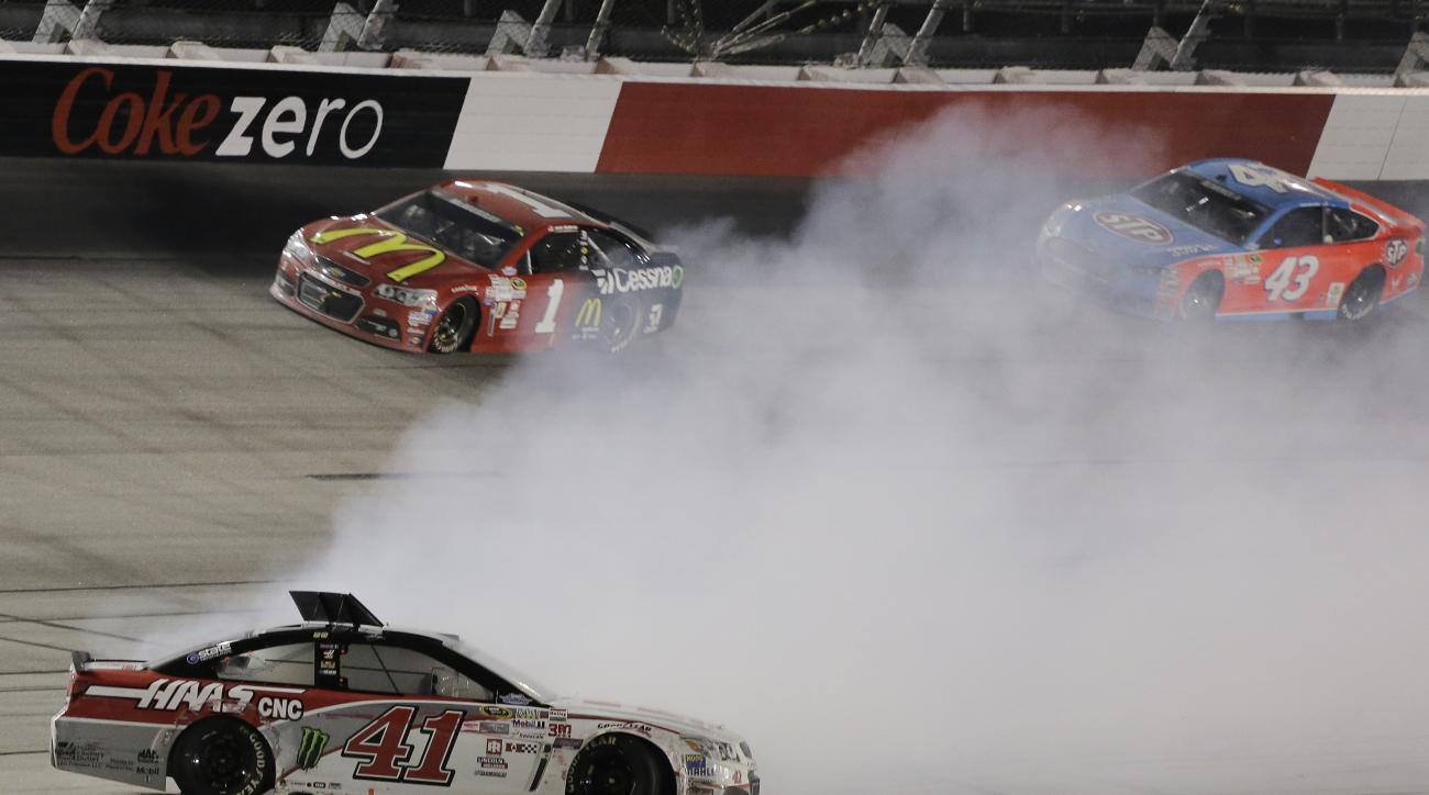 Kurt Busch (41) spins in turn four as Jamie McMurray (1) and Aric Almirola (43) drive by in a NASCAR Sprint Cup auto race at Darlington Raceway in Darlington, S.C., Sunday, Sept. 6, 2015. (AP Photo/Terry Renna)